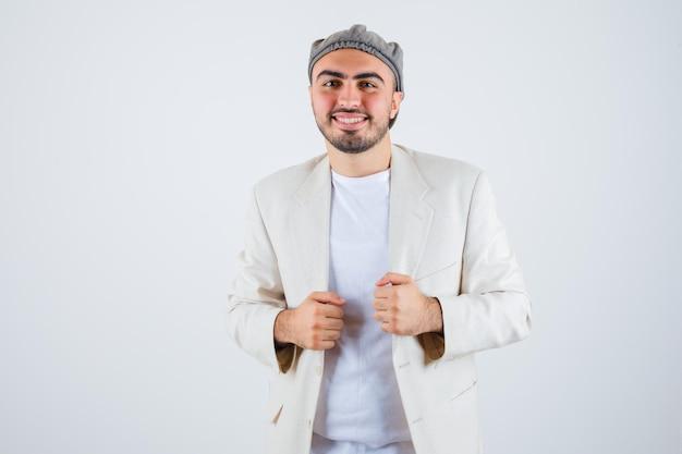 Jeune homme en t-shirt blanc, veste et casquette grise serrant les poings et ayant l'air heureux