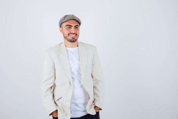 Jeune homme en t-shirt blanc, veste et casquette grise tenant les mains dans la poche et l'air heureux