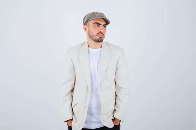 Jeune homme en t-shirt blanc, veste et casquette grise tenant les mains dans la poche et l'air pensif
