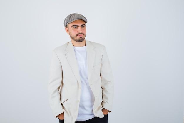 Jeune homme en t-shirt blanc, veste et casquette grise tenant les mains dans la poche et à la recherche de sérieux
