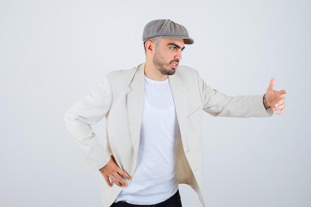 Jeune homme en t-shirt blanc, veste et casquette grise tendant la main comme tenant quelque chose tout en étirant une main comme tenant quelque chose et ayant l'air sérieux
