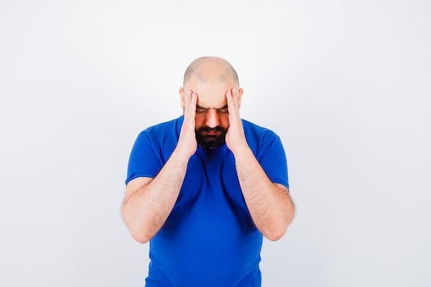 Jeune homme en t-shirt bleu ayant un mal de tête