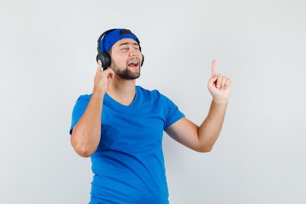 Jeune homme en t-shirt bleu et casquette appréciant la musique avec des écouteurs avec le doigt vers le haut