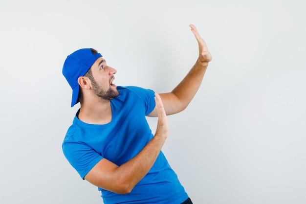 Jeune homme en t-shirt bleu et casquette montrant le geste d'arrêt et à la peur