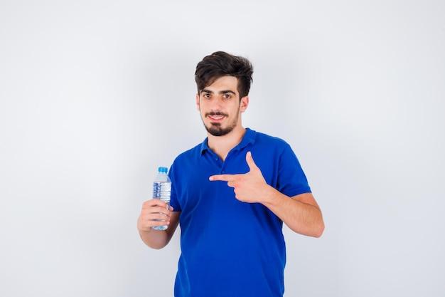 Jeune homme en t-shirt bleu tenant une bouteille d'eau et pointant vers elle avec l'index et à l'optimisme