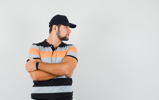 Jeune homme en t-shirt, casquette debout avec les bras croisés tout en regardant de côté et à la vue de face, focalisée.