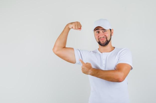 Jeune homme en t-shirt, casquette pointant sur le muscle de son bras et à la satisfaction de soi, vue de face.