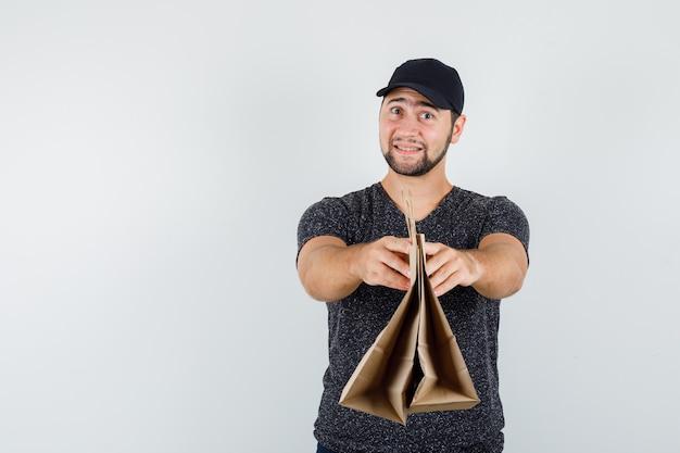 Jeune homme en t-shirt et casquette présentant des sacs en papier et à la joyeuse