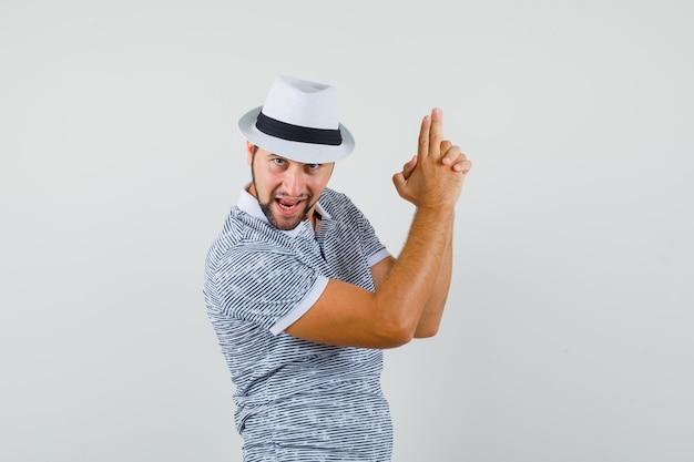 Jeune homme en t-shirt, chapeau faisant un geste de tir et l'air confiant, vue de face.