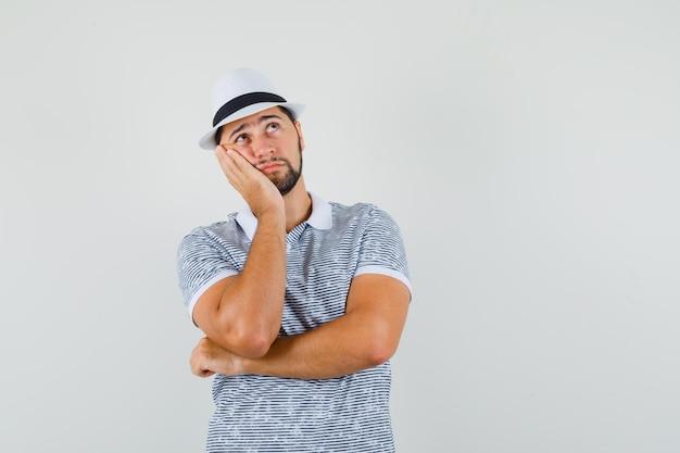Jeune homme en t-shirt, chapeau levant la paume sur la joue et l'air réfléchi, vue de face.