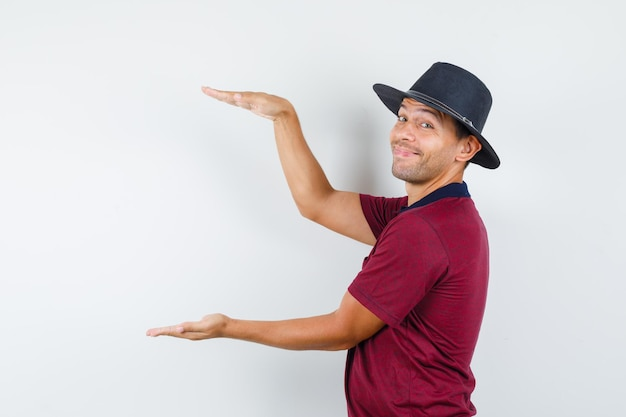 Jeune homme en t-shirt, chapeau montrant un signe de grande taille et l'air joyeux.