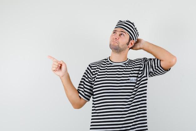 Jeune homme en t-shirt, chapeau pointant de côté et à la vue de face, hésitant.