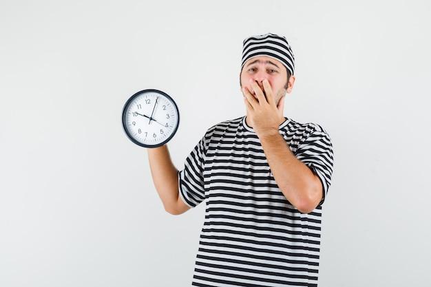 Jeune homme en t-shirt, chapeau tenant une horloge murale et regardant anxieux, vue de face.