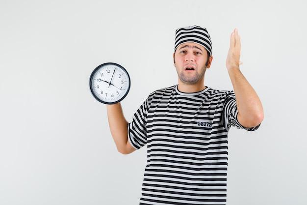 Jeune homme en t-shirt, chapeau tenant une horloge murale et regardant inquiet, vue de face.