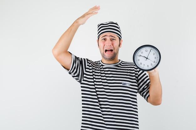 Jeune homme en t-shirt, chapeau tenant une horloge murale et regardant nostalgique, vue de face.