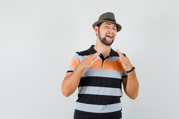 Jeune homme en t-shirt, chapeau tirant son t-shirt avec les doigts et à la fierté, vue de face.