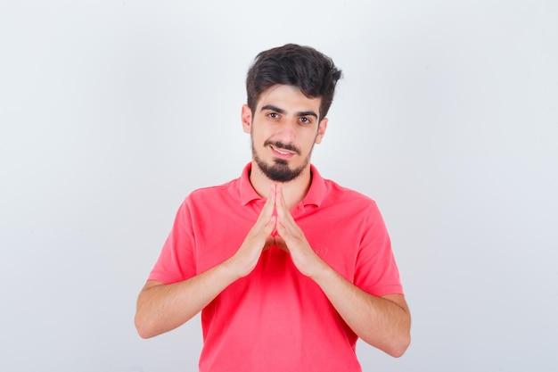 Jeune homme en t-shirt faisant un geste sur le toit de la maison et ayant l'air mignon, vue de face.