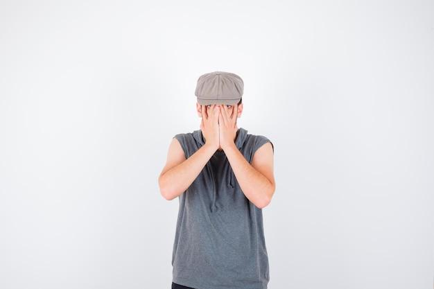 Jeune homme en t-shirt gris et casquette couvrant le visage avec les mains et l'air ennuyé
