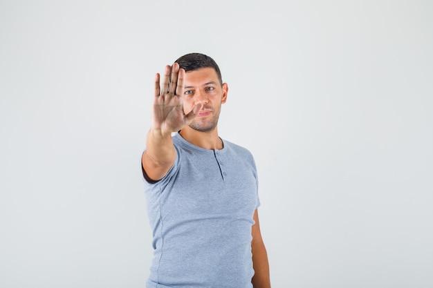 Jeune homme en t-shirt gris montrant sa main sale avec paume vers le haut