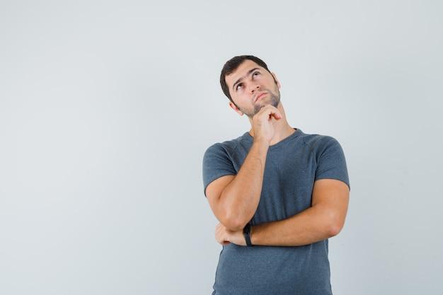 Jeune homme en t-shirt gris soutenant le menton sur place et à la pensif