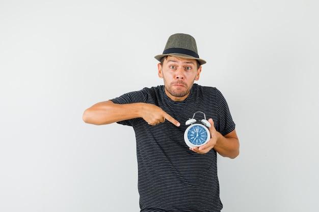 Jeune homme en t-shirt hat pointant sur le réveil et l'air inquiet