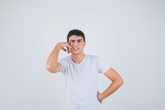 Jeune homme en t-shirt lui mordant les ongles et regardant pensif, vue de face.