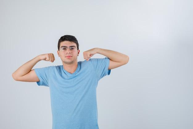 Jeune homme en t-shirt montrant le geste des muscles et l'air confiant, vue de face.