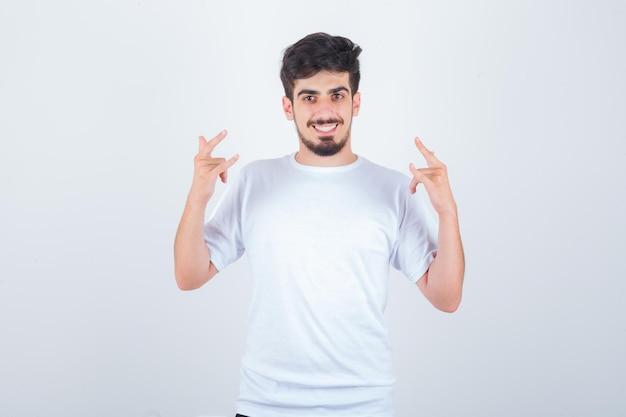 Jeune homme en t-shirt montrant je t'aime geste et à la joie