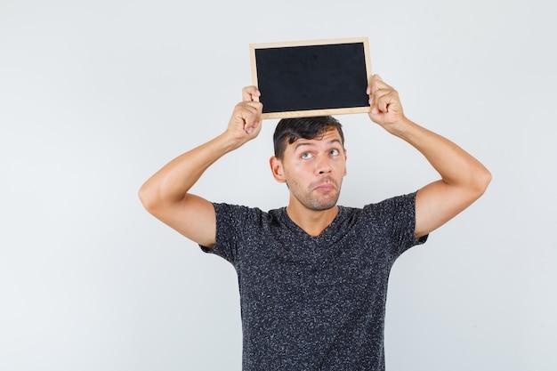 Jeune homme en t-shirt noir soulevant du carton noir sur sa tête et à la vue réfléchie, de face.
