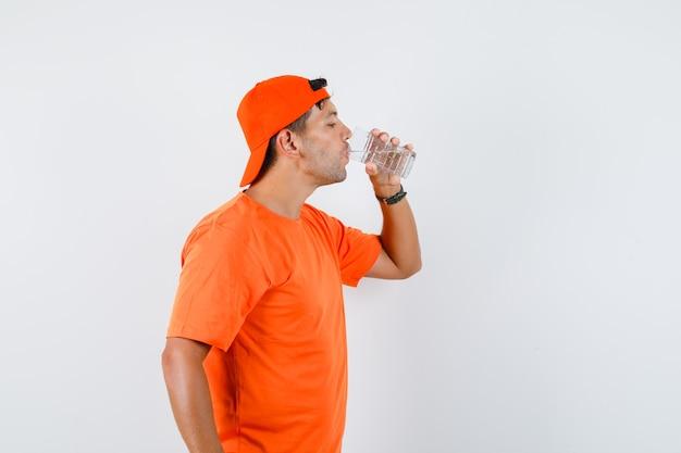 Jeune homme en t-shirt orange et casquette eau potable