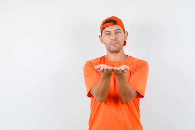 Jeune homme en t-shirt orange et casquette gardant les mains ensemble comme présentant quelque chose et à la douce
