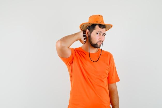 Jeune homme en t-shirt orange, chapeau touchant son cou avec les doigts et beau, vue de face.