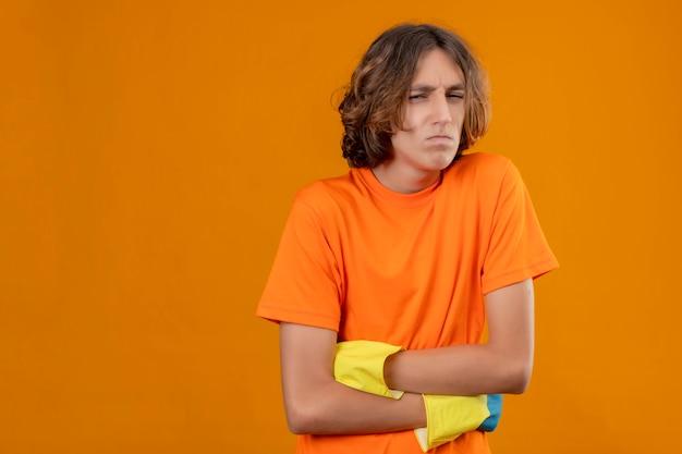 Jeune homme en t-shirt orange portant des gants en caoutchouc à la recherche de mal en se serrant ayant mal au ventre debout sur fond jaune