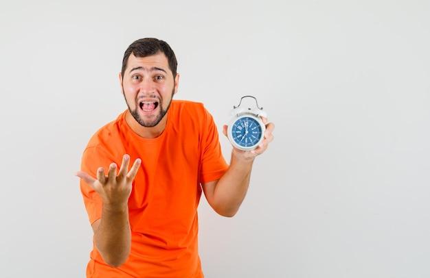 Jeune homme en t-shirt orange tenant un réveil et criant, vue de face.