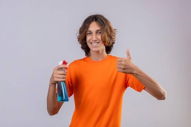 Jeune homme en t-shirt orange tenant un spray de nettoyage souriant joyeusement regardant la caméra montrant les pouces vers le haut debout sur fond blanc