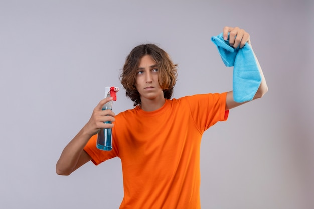 Jeune homme en t-shirt orange tenant un spray de nettoyage et un tapis à la fatigue et l'ennui debout sur fond blanc