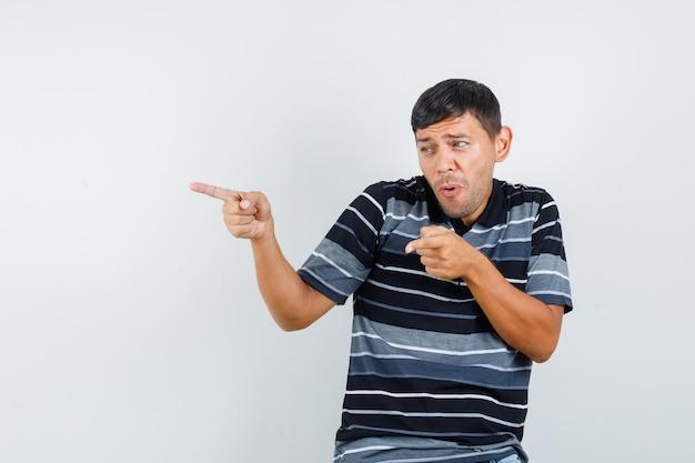 Jeune homme en t-shirt pointant sur le côté et l'air amusé, vue de face.