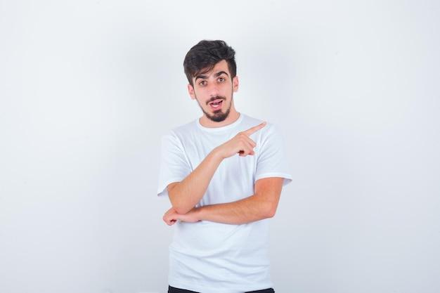 Jeune homme en t-shirt pointant vers le coin supérieur droit et l'air étonné