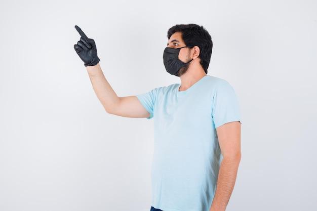 Jeune homme en t-shirt pointant vers le coin supérieur gauche et regardant concentré, vue de face.