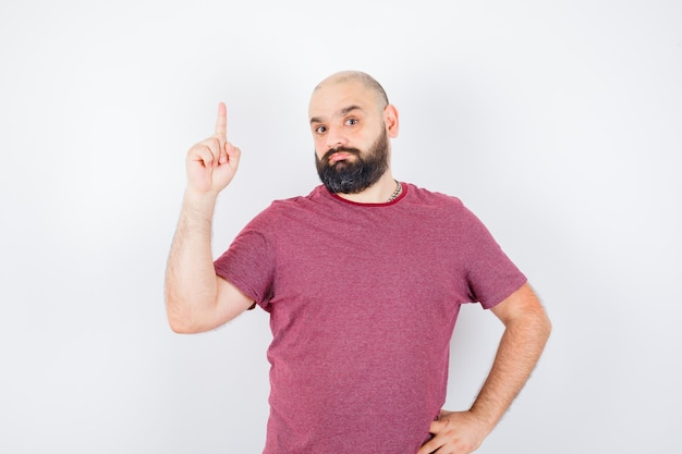 Jeune homme en t-shirt pointant vers le haut et se demandant, vue de face.