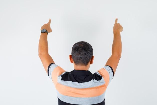 Jeune homme en t-shirt pointant vers le haut et à la vue confiante, arrière.
