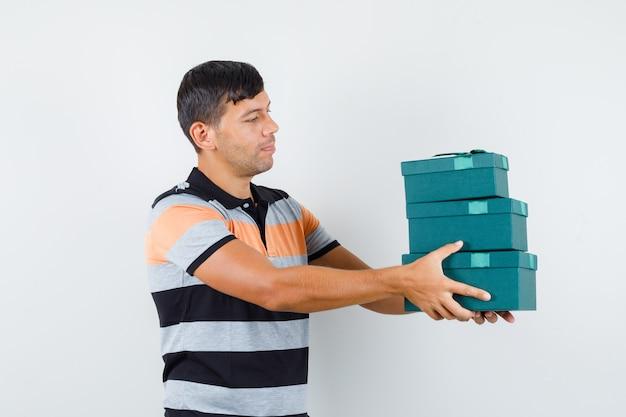 Jeune homme en t-shirt présentant des coffrets cadeaux et à la joyeuse