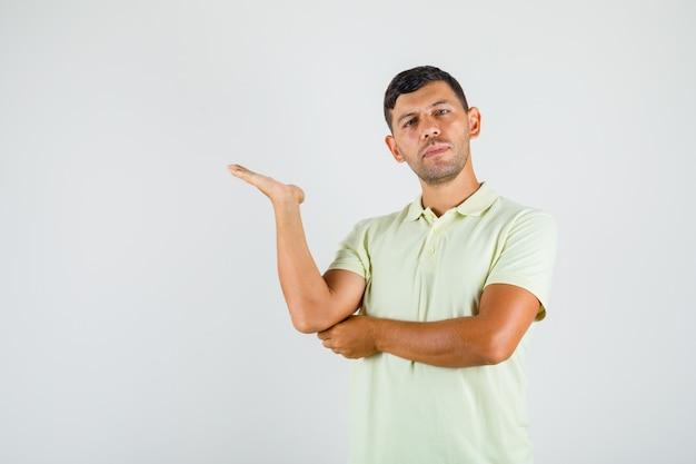 Jeune homme en t-shirt présentant et pointant avec paume ouverte et à la confiance