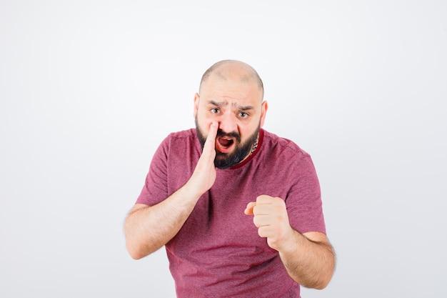 Jeune homme en t-shirt rose criant tout en levant le poing et l'air énergique, vue de face.