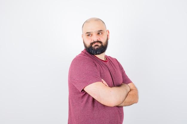 Jeune homme en t-shirt rose debout les bras croisés, détournant les yeux et l'air sérieux, vue de face.