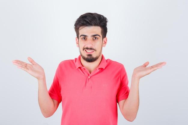 Jeune homme en t-shirt rose faisant un geste d'écailles et ayant l'air confiant, vue de face.