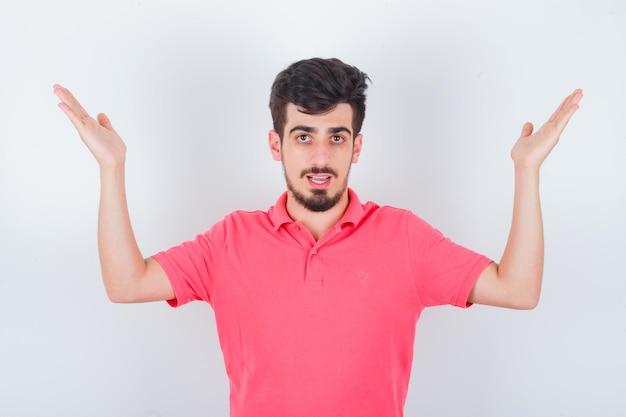 Jeune homme en t-shirt rose levant les mains et l'air confiant, vue de face.