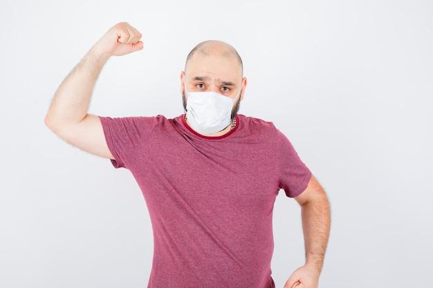 Jeune homme en t-shirt rose, masque montrant les muscles de ses bras et semblant flexible, vue de face.