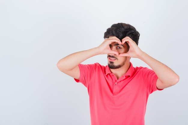 Jeune homme en t-shirt rose montrant le geste du cœur et l'air confiant, vue de face.