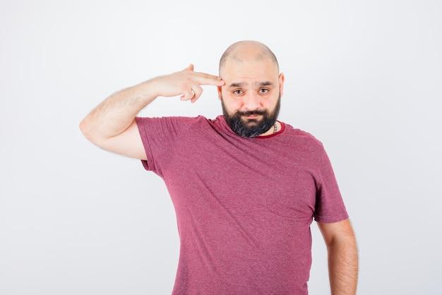 Jeune homme en t-shirt rose montrant le geste du pistolet et l'air lugubre, vue de face.